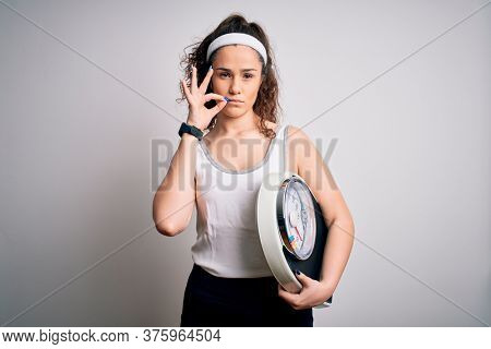 Young beautiful woman with curly hair holding weighing machine over white background mouth and lips shut as zip with fingers. Secret and silent, taboo talking