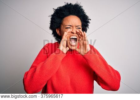 Young beautiful African American afro woman with curly hair wearing red casual sweater Shouting angry out loud with hands over mouth