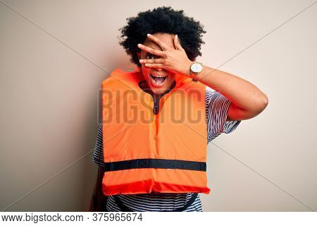 Young African American afro woman with curly hair wearing orange protection lifejacket peeking in shock covering face and eyes with hand, looking through fingers with embarrassed expression.