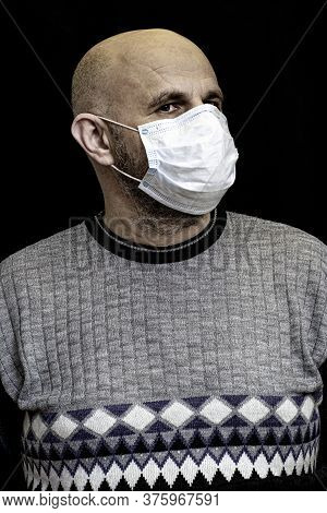 Bald Man On A Black Background In The Hygienic Medical Mask