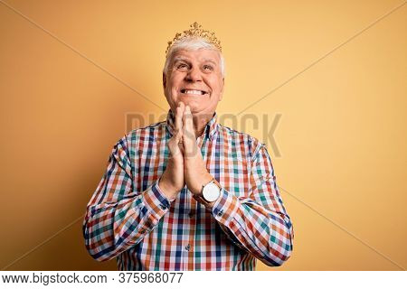 Senior handsome hoary man wearing golden crown of king over isolated yellow background begging and praying with hands together with hope expression on face very emotional and worried. Begging.