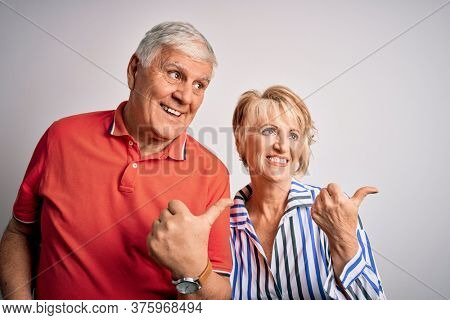 Senior beautiful couple standing together over isolated white background smiling with happy face looking and pointing to the side with thumb up.