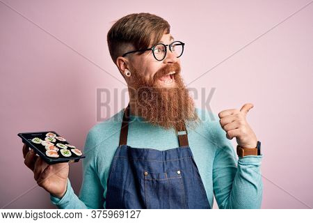 Redhead Irish cook man with beard holding maki sushi tray over isolated background pointing and showing with thumb up to the side with happy face smiling