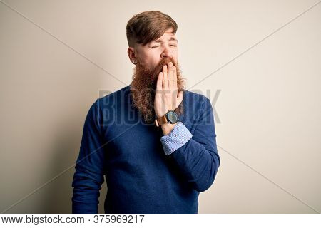 Handsome Irish redhead business man with beard standing over isolated background bored yawning tired covering mouth with hand. Restless and sleepiness.