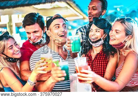 Happy Multiethnic People Drinking At Night Bar With Open Face Masks - New Normal Summer Concept With