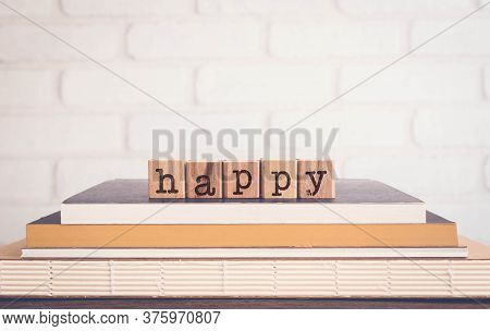 Letters Word Happy On Block Cubes On Top Of Books And Wooden Table With White Bricks Background, Bla