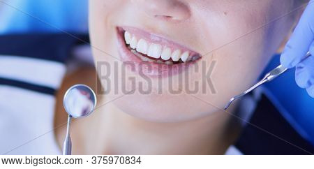 Young Female patient with pretty smile examining dental inspection at dentist office.