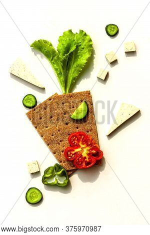 Slices Of Cucumber, Tomato, Tofu And Sweet Peper With Lettuce Leaves And Rye Crispbread On White Bac