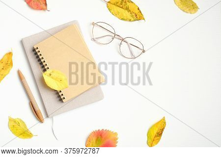 Autumn Flatlay Composition. Women Fashion Glasses, Paper Notebook, Fallen Leaves On White Background
