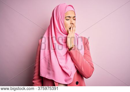 Young beautiful girl wearing muslim hijab standing over isolated pink background bored yawning tired covering mouth with hand. Restless and sleepiness.