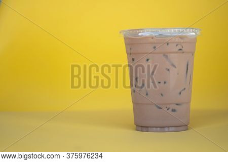 Cold Mocha Coffee Drink In Takeaway Glass On Yellow Background