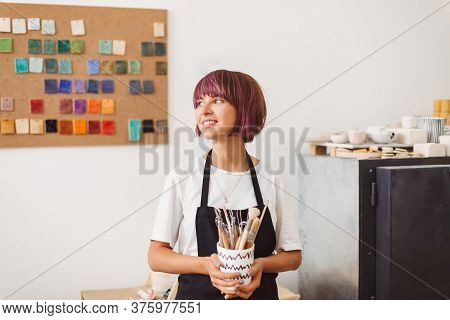 Pretty Girl With Colorful Hair In Black Apron And White T-shirt Holding Mug With Pottery Tools In Ha