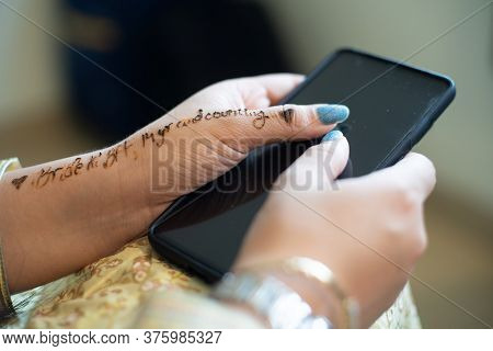 Young Indian Girl Decked In White Gold Dress Preparing For A Wedding Holding Phone With Words Bride