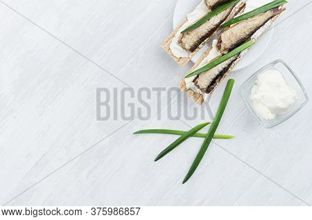 Summer Light Open Sandwiches On Crisps Bread With Fish Preserves, Feta Cheese, Green Onion Sprig On