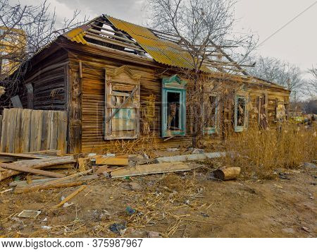 Abandoned Wooden House. Wooden Hut In Shanties With Reed Growing In Front Of.
