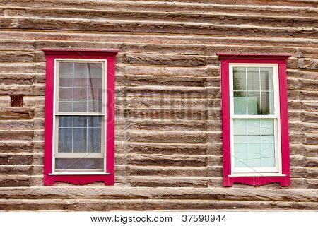 Red framed windows in log house wall architecture