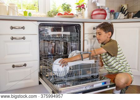 Little boy loading the dishwasher at home