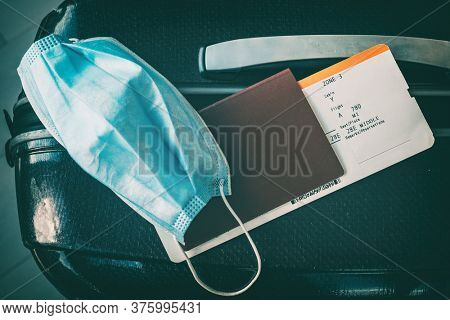 COVID-19 travel restriction due to corona virus mask wearing obligatory in airport and airplane flights to Europe, Asia. Passport, ticket and suitcase ready for holidays.