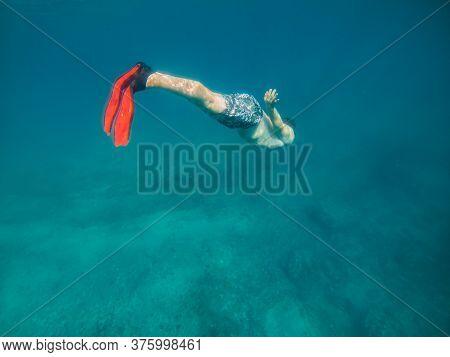 Man In Underwater In Flippers Looking At Sea Bottom