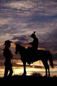 A cowboy is sitting on a horse in the sunset swinging a rope with the silhouette of a cowgirl standing off to his side holding on to her rope. poster