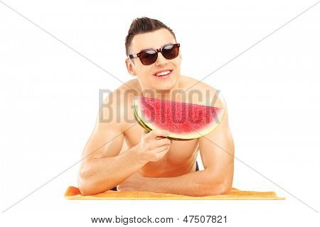 Young man laying on a beach towel and eating a slice of watermelon isolated on white background