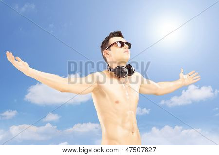 Male tourist with speakerphones spreading his arms and gesturing pleasure outside