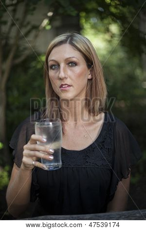 Blonde Woman With Beautiful Blue Eyes And Glass Of Water