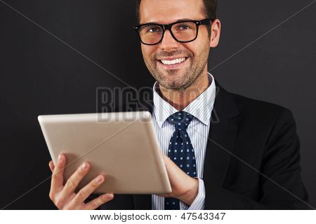 Businessman wearing glasses using digital tablet
