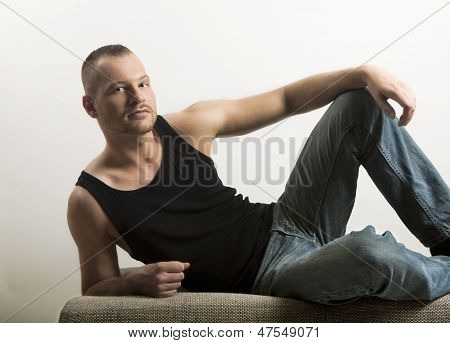 Man In Muscle Shirt Lying On A Sofa