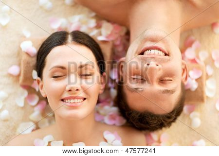faces of couple in spa salon lying on the massage desks
