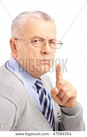 Grumpy mature man gesturing silence with a finger isolated on white background