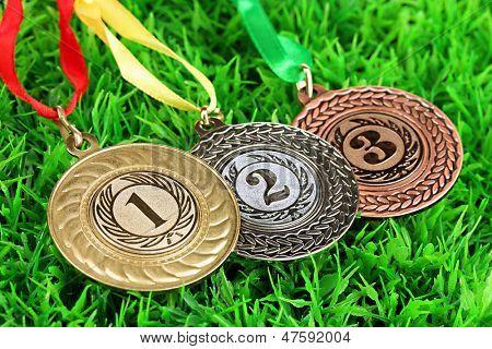 Three medals on grass background