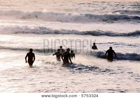 A group of smimmers / surfers running in the sea at the famous surfing Fistral Bay, Cornwall, UK