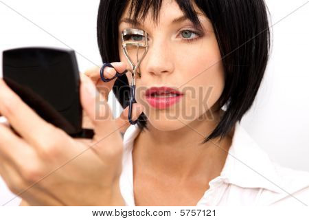 Beautiful Woman using an eyelash curler