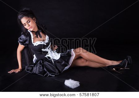 Beautiful seductive woman posing sitting on the floor in a cute little maids outfit with miniskirt poster
