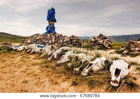 Mongolian stone shrine or Ovoo with ceremonial prayer flags called khadag and horse skulls poster