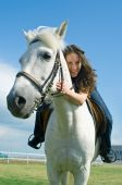 The young smiling girl embraces a white horse poster