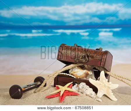 Ancient chest with sea cockleshells, hourglasses and a rope on sand poster