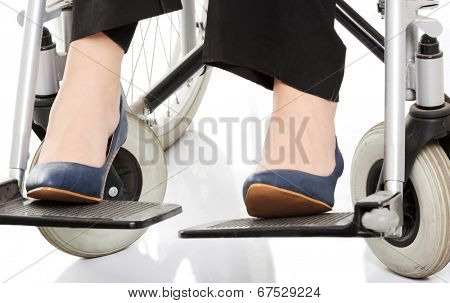 Close up on female's legs and shoues on wheelchair. Over white background.