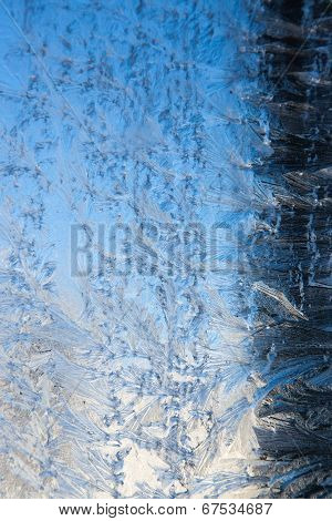 A winter frost pattern spread across glass with a dark fading to light background. poster