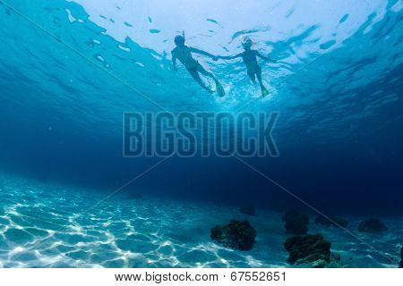Underwater shot of the couple snorkeling on sea surface