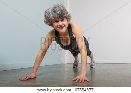 Middle Aged Female Sports Trainer In Pushup Position
