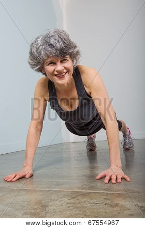 Smiling Middle Aged Sports Trainer In Pushup Position