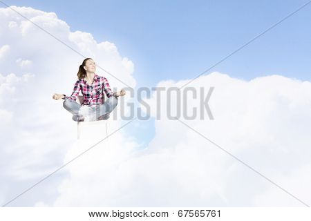 Young woman sitting on chair and meditating