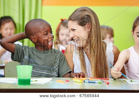 Nursery teacher and children having fun together in a kindergarten group