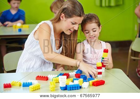 Nursery teacher and girl playing with building bricks in a kindergarten