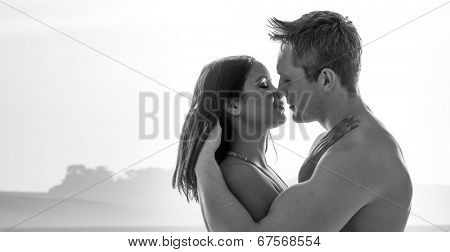 Greyscale image of an attractive naked young couple enjoying a romantic kiss standing sideways in an intimate embrace against a backdrop of distant misty mountains