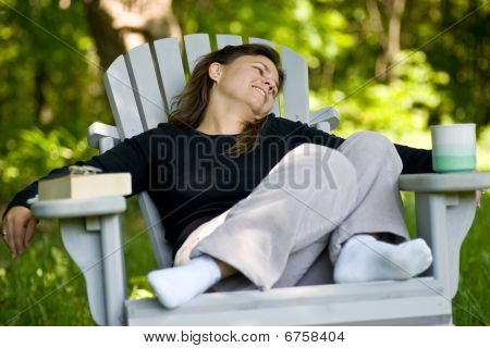 Woman sitting in a chair with coffee cup and book
