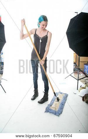 A young woman sweeps up dirt with her broom on the set of a Photo Shoot in between Photo Sessions.  Isolated on white with room for your text.
