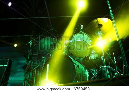 Drumset on an empty stage light with strong backlight